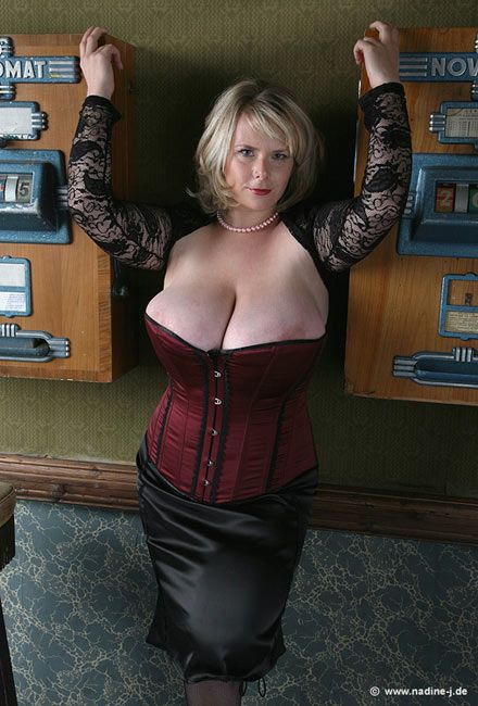 Big breasted woman in corset giving blowjob